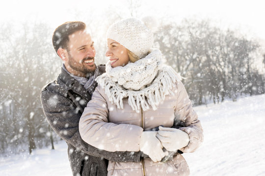 Smiling couple hugging and enjoying outdoors while falling snow