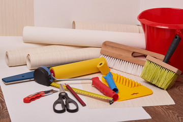 Rolls of wallpapers and various tools for wallpapering.