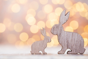 Wooden easter rabbits on the bokeh background.