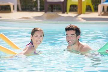 Couple in swimming pool using floats