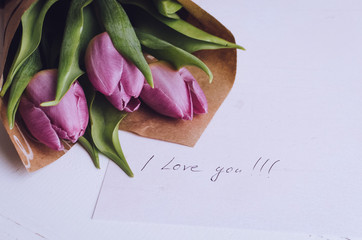 Bouquet of pink tulips with notes I LOVE YOU
