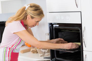 woman putting pie in the oven