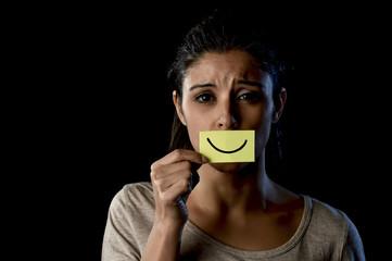 Latin sad depressed latin girl holding paper hiding her mouth behind fake drawn smile