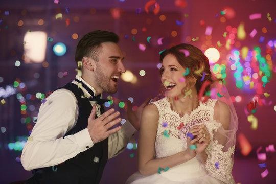 Cute happy wedding couple against defocused lights