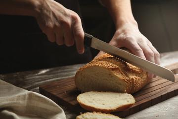 Male hands cutting wheaten bread, closeup