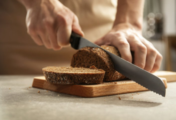 Male hands cutting homemade bread, closeup