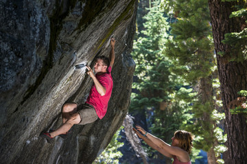 A man climbs (Midnight Train - V7) at the Saddle Boulders while his friends spot him on Donner Summit near Truckee, California.