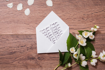 """The inscription """"I love you"""" writing on the envelope calligraphy. Flowers and jasmine petals on wooden background. Greeting card. Conceptual photography. Wedding invitation card. Valentine day.;"""