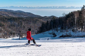 Girl snowboarding on the mountain slope