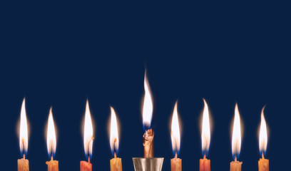Chanukah candles burning low isolated on dark background.