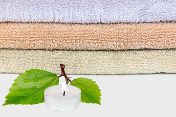 Tea light candle, green leaves, water droplets. Towel background.