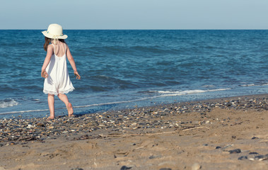 Little girl in white dress walking alone the sea, playing on the seashore at the sunset