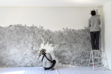 Two worker use brush for color paint concrete Loft style on wall