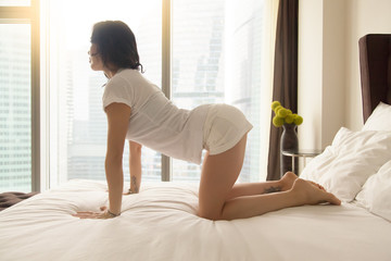 Young attractive sporty woman practicing yoga on bed after waking up, doing asana paired with Cat Pose on the exhale exercise, Cow, Bitilasana pose, working out wearing white home wear, full length