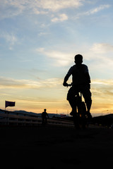 silhouette of young man  cyclist on sunrise sky with clouds