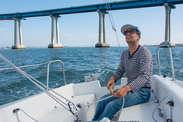 A man in a striped sweater, jeans, a blue cap and red sneakers controls sailing boat. Boy holds the tiller of a sailing boat in the hands. The bridge on background. Adventure. Sailor