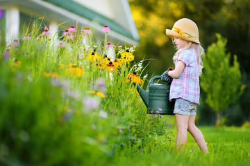 Cute little girl watering flowers in the garden at summer