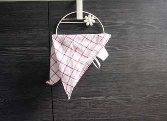 Hand towel hanging on a wooden board.