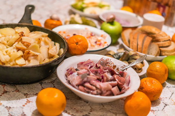 Country dinner with roast potatoes, smoked fish, bread, coleslaw and fruits