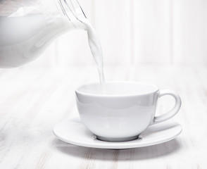 Milk is poured into a cup of pitcher on white background wooden