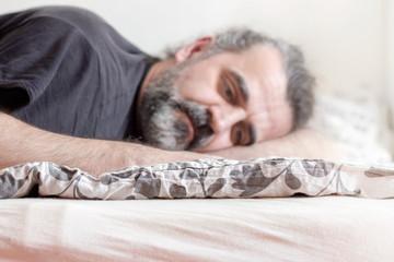 Man lying depressed in a bed in bedroom