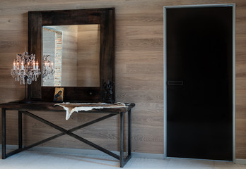 In the room are antique mirror and brass crystal light. Modern interior design of hallway.