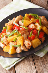 fried chicken with pineapple and vegetables in sweet and sour sauce close-up. vertical