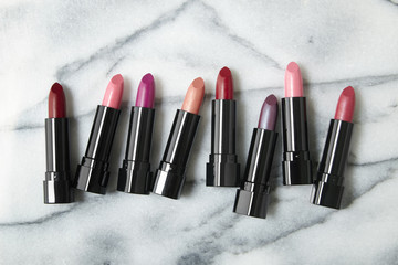 A selection of lipstick make up arranged on a white marble counter background