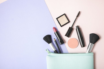 Make up products spilling out of a pastel blue cosmetics bag, on a pink and purple background with blank space at side