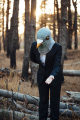 Creepy man in a suit and a rubber bird mask, standing in the sunset forest, inviting to go with him