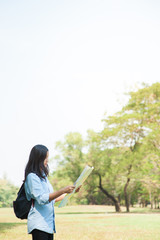 Women traveler with backpack checks map to find directions in the park of Thailand,active people lifestyle