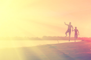 Naked man and a woman running on the beach at sunset