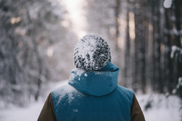 Young man standing all alone in the winter snowy forest