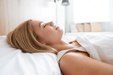 Close up image of young woman sleeping on bed