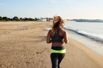 Sportswoman running on beach.