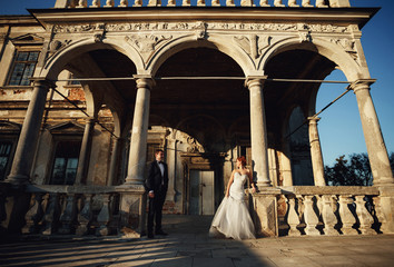 couple are photographed on a wide balcony beautiful building