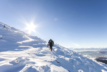 A male mountaineer walking uphill on a glacier. Mountaineer reac
