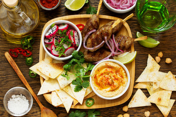Kyufta (barbecue) of lamb with snacks (radish salad, chips and hummus.)