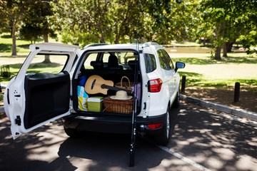 Guitar, fishing rod, picnic basket in car trunk