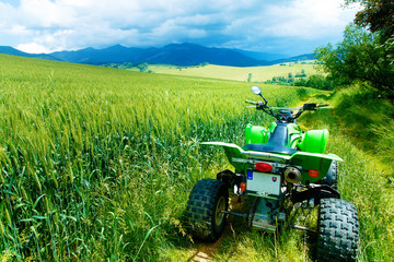 Green Quad in landscape on road in field.