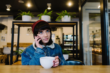 Young happy hipster girl talking on the phone and drinking tea in a beautiful cafe