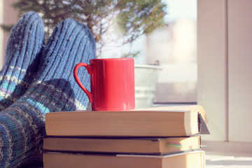 warming atmosphere holiday home/ red mug on a pile of books on background feet in warm socks on a table next to the window