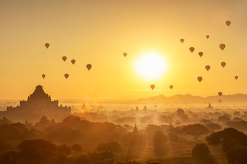 Scenic sunrise with many hot air balloons above Bagan in Myanmar. Bagan is an ancient city with thousands of historic buddhist temples and stupas.