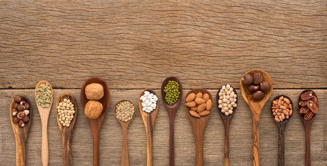 Different kind of beans and lentils in wooden spoon on wood back