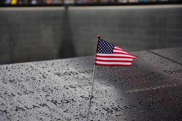Memorial at Ground Zero Manhattan for September 11 Terrorist Attack with an American Flag Standing near the Names of Victims Engraved