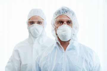 Man and woman in protective masks, eyeglasses and coveralls