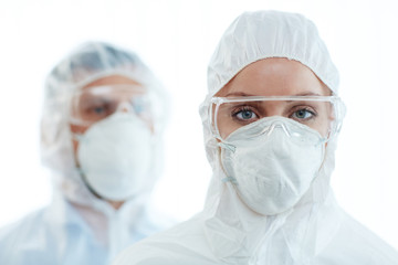 Young female in coveralls, eyeglasses and respirator looking at camera with her colleague on background
