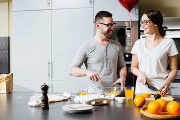 Young husband and wife preparing food for Valentine day