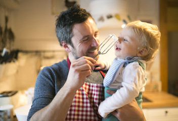 Father and baby boy in kitchen baking a cake