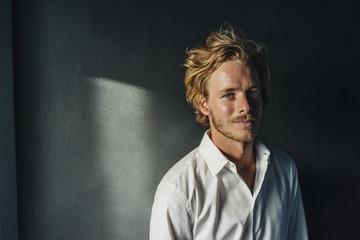Portrait of smiling blond man wearing white shirt